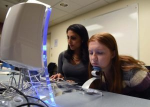 Elsa Weltzien, a project team member, poses for the Reveal Imager as Jessica Mounessa runs the machine.