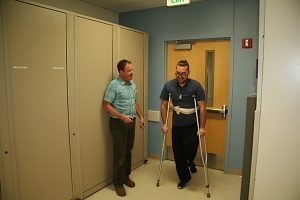 The patient begins walking with his physical therapist.