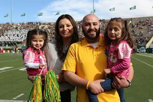 Josh Romero, his wife, Vanessa, and their two girls enjoy the CSU game