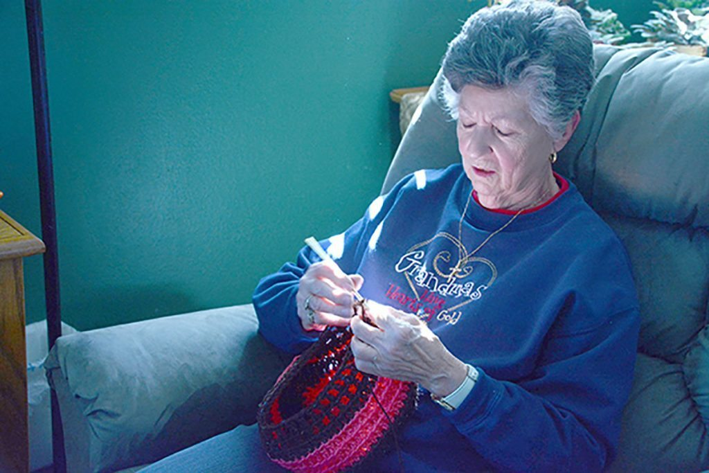 A woman crochets hats for cancer patients.
