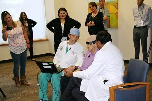 bionic eye patient sits with his doctors.
