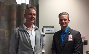 Dr. Gregory B. Collins, an emergency department physician at UCHealth Memorial Hospital, and Mark Mayes, director of Emergency Services at Memorial, stand outside one of the intake rooms in the department, where patients see a doctor within 15 minutes of arrival.