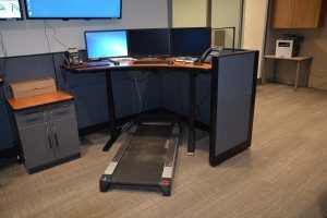 A treadmill at one of the workstations in the transfer center will allow staff to stay active during long hours. All workstations are built for standing while working.