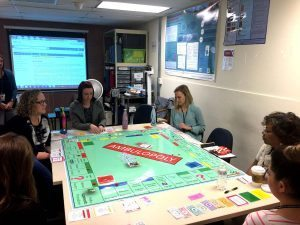 group of students sit around what looks like a monopoly board during clinical orientation