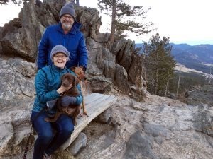 Bill and his wife holding the dog on top of a ridge.