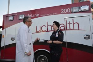 DocLine Executive Director Richard Zane speaks with UCH Emergency Department nurse Dawn King in front of the newly branded UCHealth LifeLine critical care ambulance.