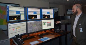 Leeret at one of the DocLine workstations with six screens