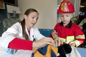 ER doctor puts a cast on a stuffed animal while boy in a fire costume watches.