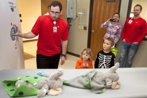 two elephant stuffed animals go through an x-ray machine while kids and parents watch
