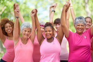 Women in pink shirts hold their hands up in excitement. Women's sexual health is important after cancer.