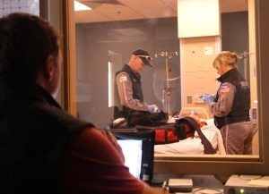 In this photo, Air Link's certified flight registered nurses Leanna Harpman and Duane Rorie work on a simulation patient while simulation educator and flight RN Ryan Bushmaker controsl the scenario from behind one-way glass.
