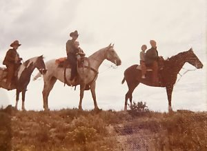 O. Rex Story and his four children are shown on horses along the Laramie River.