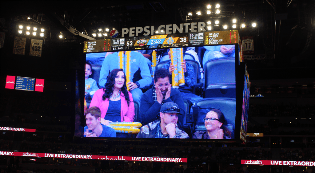 Val Sotelo, a UCHealth Memorial Hospital employee, is overwhelmed with emotion when her story is shared during a Denver Nuggets game. Sotelo was honored as part of UCHealth's Moments to Shine program.