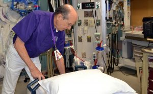 Volunteer Bob Allen is shown adjusting a bed in the Emergency Room at Poudre Valley Hospital.