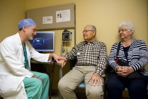 Dr. John Carroll talks with Don and Amy Lovell in a UCHealth University of Colorado Hospital exam room.