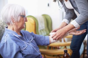 An older woman holds her arm out and gets bandaged.