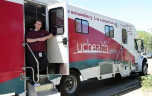 UCHealth employee stands at the door of a bus during a mobile blood drive.