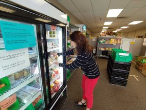 women stalks food in a food pantry in Fort Collins that addresses the whole person and is one of the ways to reduce health care costs.
