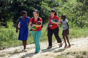 Andrea Hooley, registered nurse and transitional care case manager for UCHealth Family Medicine Center Residency, carries a child for a Haitian mother.