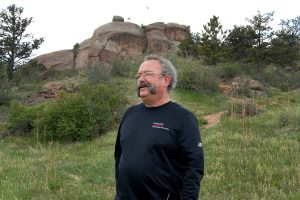 Stan Kepley stand on a trail leading up to some rocks at Kurt Goudy State Park near Cheyenne, Wyoming.