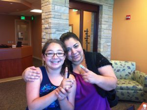 a mom and daughter hold up their fingers where they got pricked for their tests.