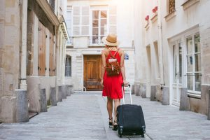 A photo of a woman pulling a suitcase down a street.