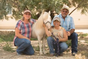Sara Millard is pictured with her mom, Vicky, and father, John, and horse, Tazz