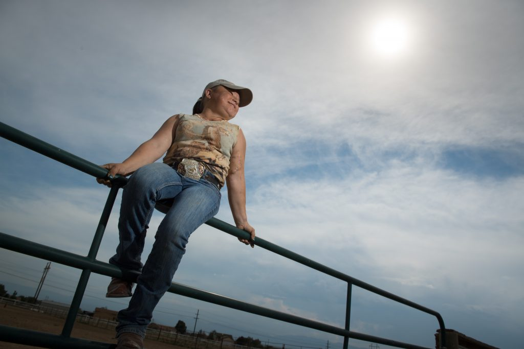 Sara Millard sits on a fence while taking a break from training for her rodeo event.