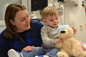 Ethan Bell reaches over to hug his teddy bear after a quick visit with the doctor during a recent Teddy Bear Hospital event at UCHealth Poudre Valley Hospital in Fort Collins