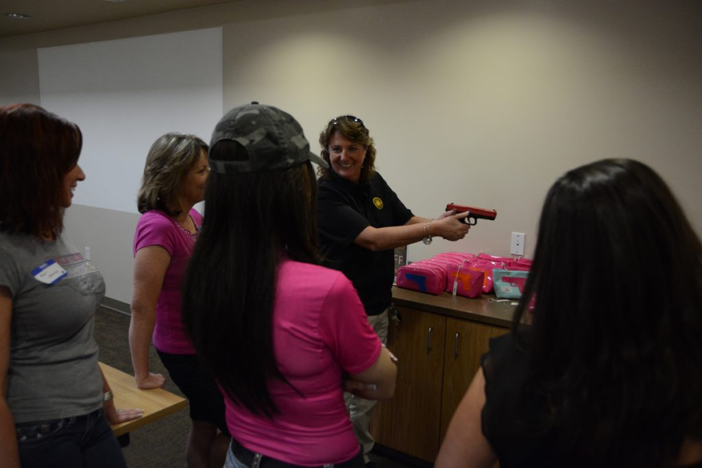 An instructor shows women how to properly hold a gun.