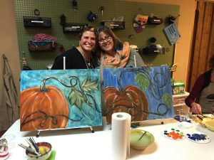 Jennifer Reid and Yvette Engel are photographed behind a craft project, including this painting project of pumpkins