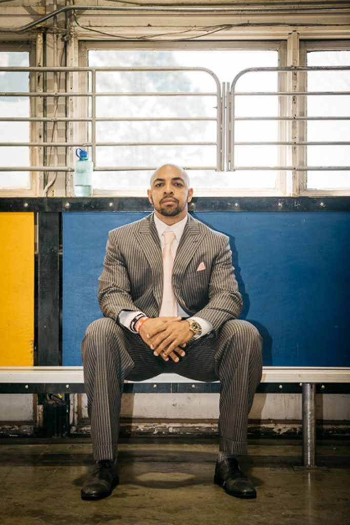 Bo Scaife, wearing a suit and tie, sitting on a bench.