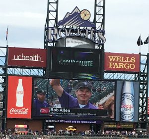 Volunteer Bob Allen is shown on the jumbotron during a Colorado Rockies baseball game.
