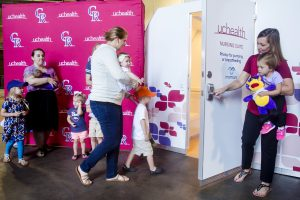 In this photo, mothers and children are shown outside a UCHealth Nursing Suite at Coors Field.