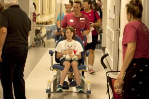 "In this photo, Stephanie Mathews, 9, gets wheeled into the UCHealth Longs Peak Hospital Emergency Department with her teddy bear, which was suffering from ""sparkle pox,"" during the UCHealth Teddy Bear Hospital event."