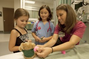 "In this photo, five-year-old Sidney Walker, left, had her teddy bear checked out by UCHealth Registered Nurse Amanda Martinez, right, and ""doctor"" Morgan Martinez, middle, during the UCHealth Teddy Bear Hospital event in Longmont."