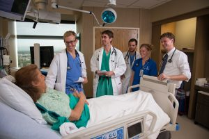 A group of physicians and providers talk with a patient who is sitting up in bed.
