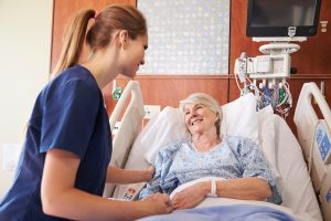 A nurse talks with a patient who is laying down in bed.