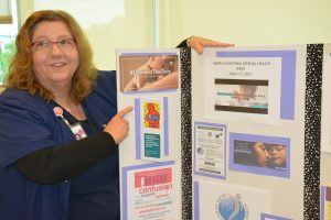 Carol Lawson, a nurse at UCHealth Memorial Hospital, is shown next to a display about postpartum depression.