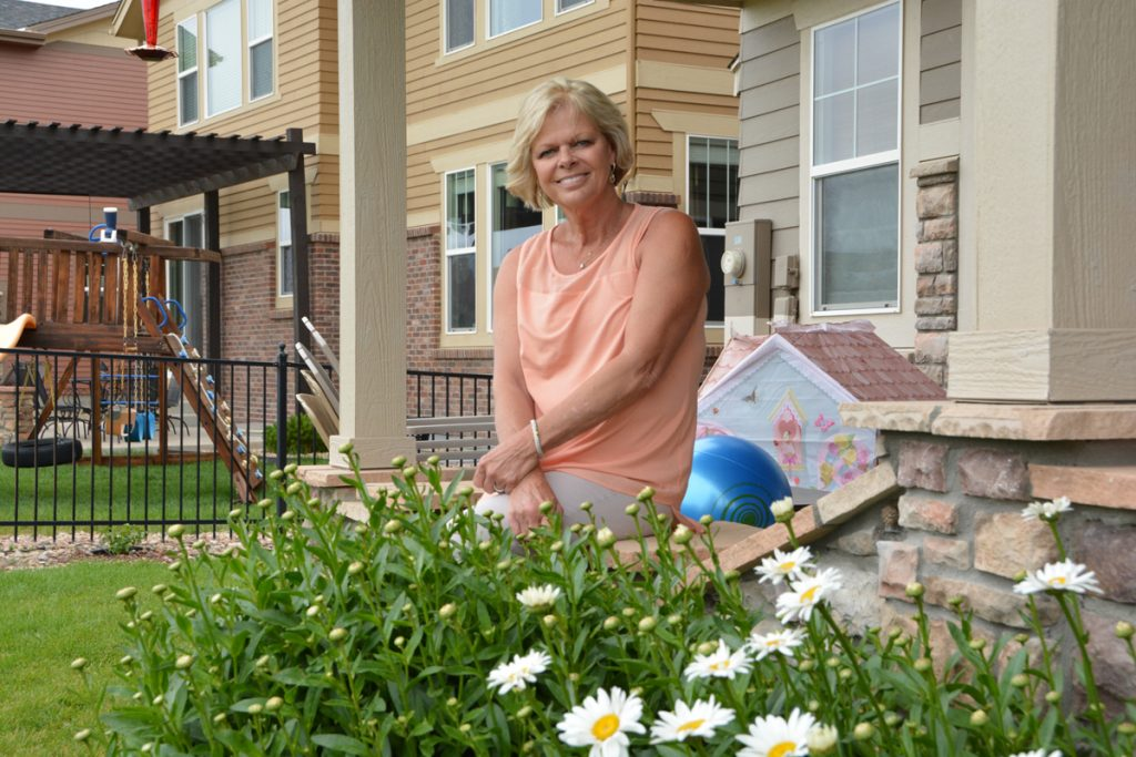 Sandy Doria is shown outside next to her garden.