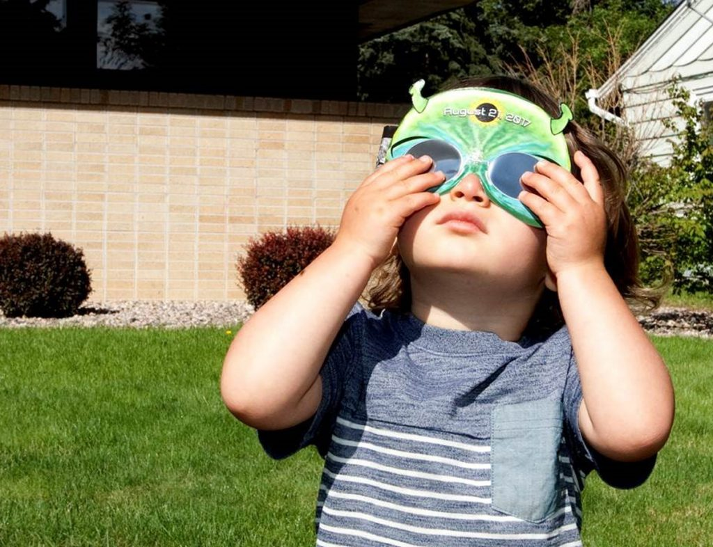 A child is shown with protective viewing glasses during a solar eclipse.
