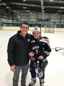 Leland Fay is pictured at a hockey rink with one of his sons.