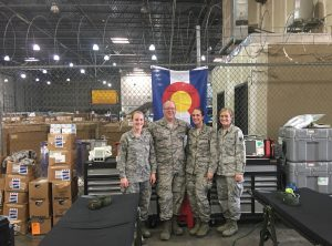UCHealth medical relief workers wearing military fatigues gather to help in Texas after the hurricanes with a Colorado flag draped behind them.