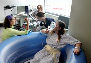 A woman breathes from a nitrous oxide mask while sitting in a water birth tub. She is surrounded by nurses who are helping her during a training before UCHealth's newest hospital opened in Longmont.