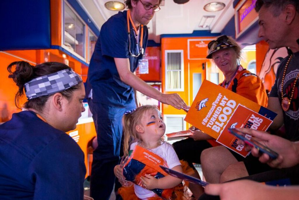 "Ambulance workers on the orange and blue Broncos Fever ambulance give information to ""patients"" including a toddler girl who holds some orange gear and looks up at her parents while they get ""treatment"" for being Bronco fans."