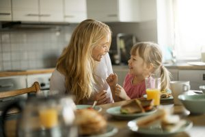 A mother and daughter smile at each other while eating breakfast in their kitchen. We see orange juice and pastries on a kitchen island.