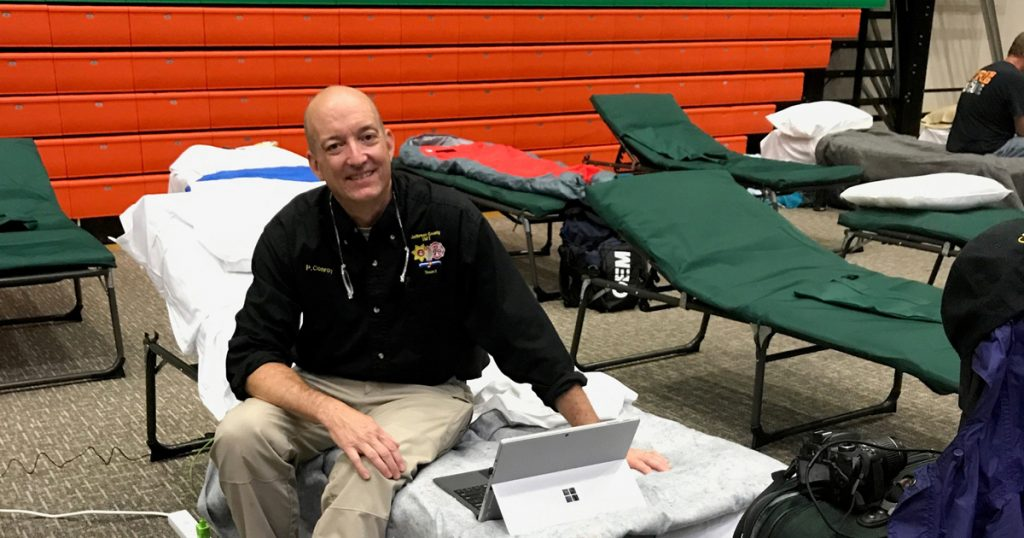 Pat Conroy, an emergency volunteer, sleeps on a cot on a basketball court after heading to Florida to help with hurricane recovery.