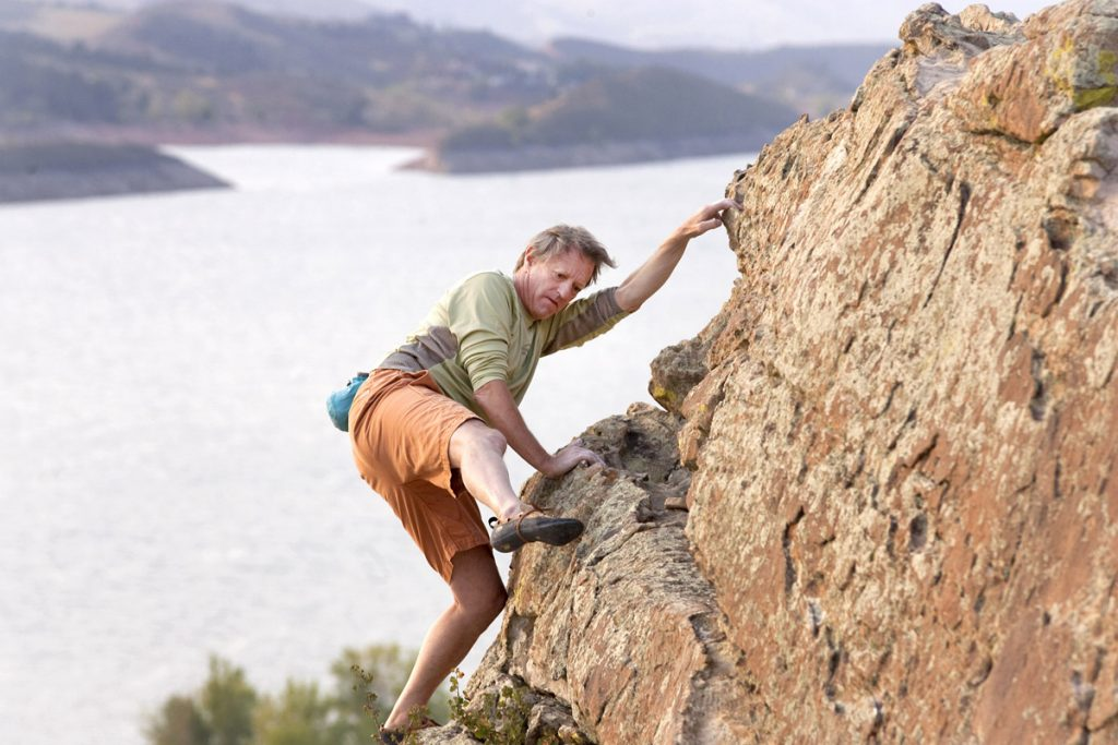 Randy Joseph climbs on some rocks above Horsetooth Reservoir in Fort Collins. He began walking and moving again soon after hip replacement surgery.