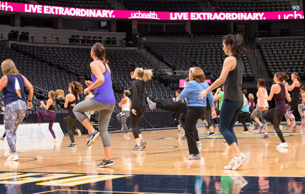 women taking a class on the floor of the Nuggets' arena.