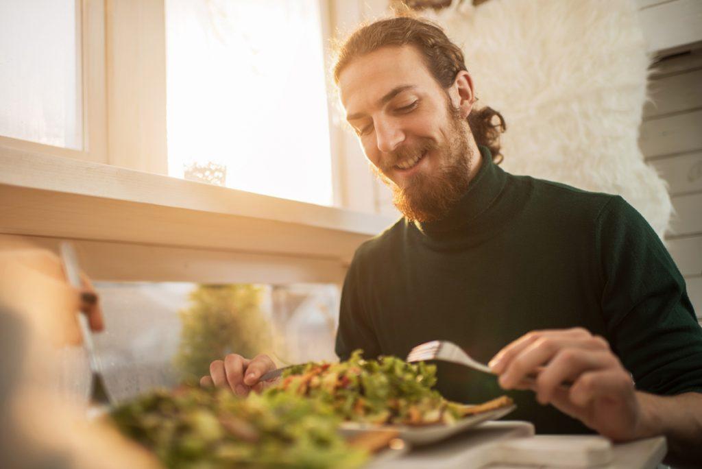 man sits at a table eating salad.